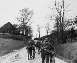 Pripadniki nemške kolesarske enote, 183. pehotna divizija, na poti proti Ptuju skozi eno od okoliških vasi, 8. april 1941. Medtem so se že začele sabotažne akcije etničnih Nemcev v Ptuju, kamor so Nemci vkorakali okrog pol treh popoldne na isti dan. Z nacističnimi zastavami okrašena mestna hiša na Ptuju aprila 1941.